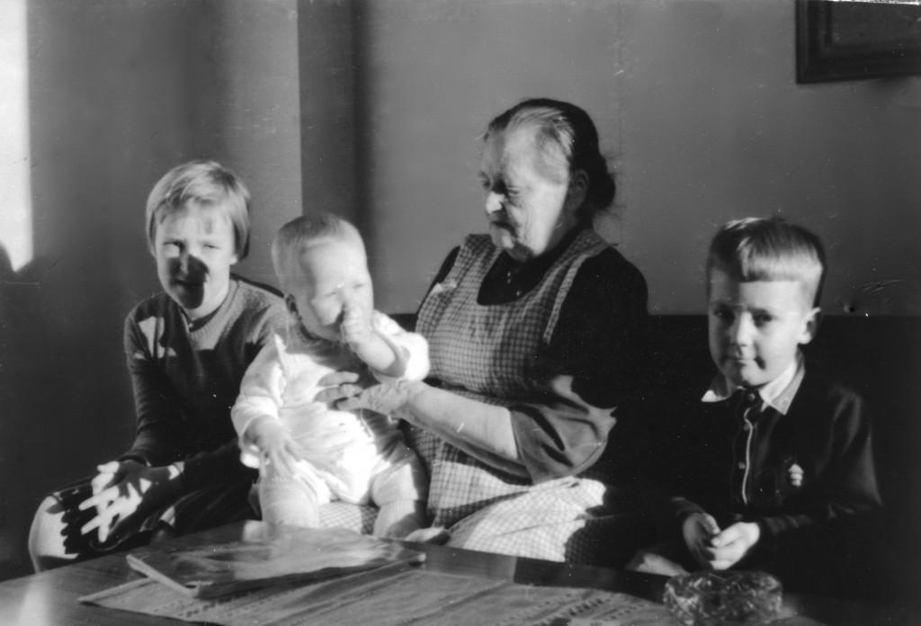Outi-sisko ja Mummo sylissään ilmeisesti serkkumme Jouko. Minä istun mummon oikealla puolella.
